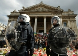 """Police in riot gear protect one of the memorials to the victims of the recent Brussels attacks, as right wing demonstrators protest near the Place de la Bourse in Brussels, Sunday, March, 27, 2016. In a sign of the tensions in the Belgian capital and the way security services are stretched across the country, Belgium's interior minister appealed to residents not to march Sunday in Brussels in solidarity with the victims.""""We understand fully the emotions,"""" Interior Minister Jan Jambon told reporters. """"We understand that everyone wants to express these feelings.""""(AP Photo/Alastair Grant)"""
