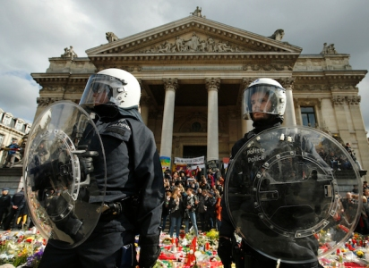 "Police in riot gear protect one of the memorials to the victims of the recent Brussels attacks, as right wing demonstrators protest near the Place de la Bourse in Brussels, Sunday, March, 27, 2016. In a sign of the tensions in the Belgian capital and the way security services are stretched across the country, Belgium's interior minister appealed to residents not to march Sunday in Brussels in solidarity with the victims.""We understand fully the emotions,"" Interior Minister Jan Jambon told reporters. ""We understand that everyone wants to express these feelings.""(AP Photo/Alastair Grant)"