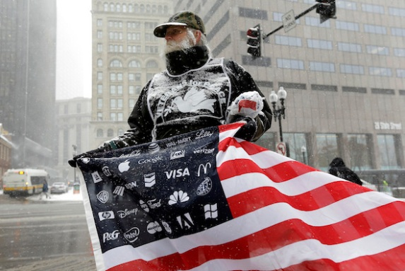Protester Bob Bowes, of Somerville, Mass., displays an American flag featuring corporate logos, outside the location of a news conference by General Electric CEO Jeff Immelt, Massachusetts Gov. Charlie Baker, and Boston Mayor Marty Walsh, Monday, April 4, 2016, in Boston. Bowes joined a protest with others outside the news conference to highlight the millions of dollars in tax breaks and public incentives used to lure the company. (AP Photo/Steven Senne)