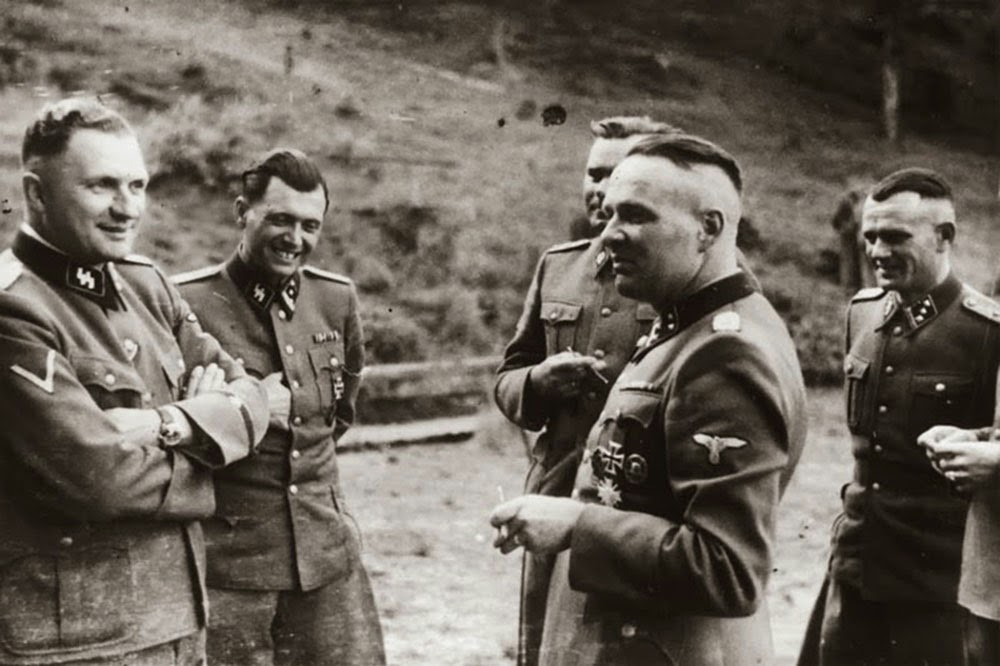 Taking a break. The second person is the notorious concentration camp doctor Josef Mengele (The Angel of the Death).