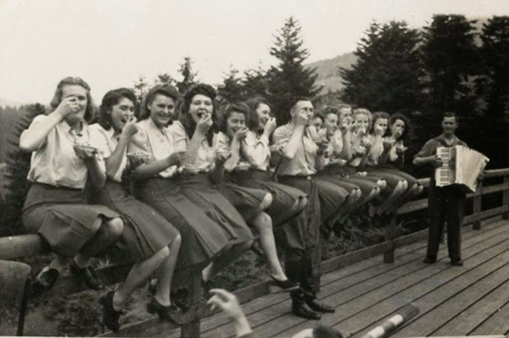 Twelve SS auxiliaries sit happily on a fence railing eating blueberries given to them by an SS officer.